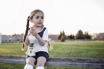 Girl with trophy looking away while sitting on bench against clear sky at park