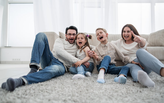 happy family sitting on the carpet in the living room