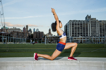 Female athlete with arms raised exercising on retaining wall by net during sunset