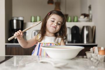 Girl preparing food on worktop at kitchen
