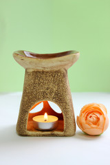 Aroma lamp with flower and candles isolated