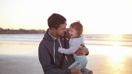 Happy father carrying daughter while standing at beach against clear sky during sunset