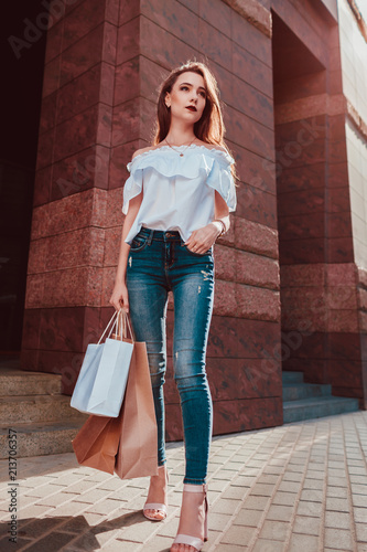 15201526 Beautiful stylish young woman with shopping bags walking on city street.  Slim model wearing closing and accessories.
