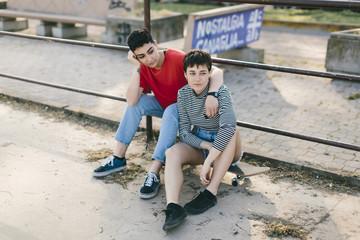 Lesbian couple sitting on skateboard by railing