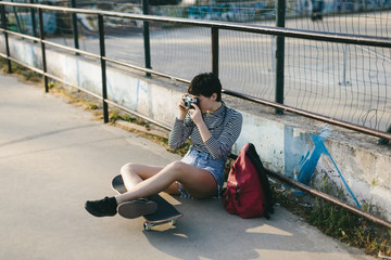 Woman taking picture while sitting outdoors