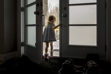 Rear view of girl standing at entrance in house