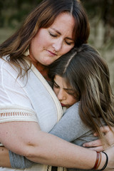 Close-up of daughter embracing mother while standing at yard