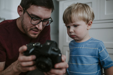 Man showing camera to baby boy at home