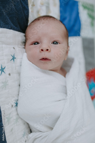 Portrait Of Newborn Baby Boy Wrapped In Blanket Lying On Bed At Home
