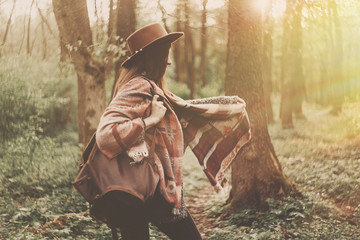 stylish hipster traveler girl in hat with backpack exploring in woods in amazing evening sunshine light. woman having fun in sunlight. space for text. atmospheric moment. wanderlust