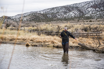 Man holding fishing rod while standing in river against mountains