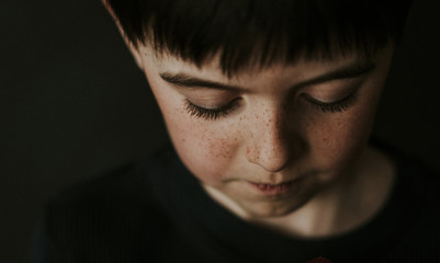 High angle close-up of boy with freckles over black background