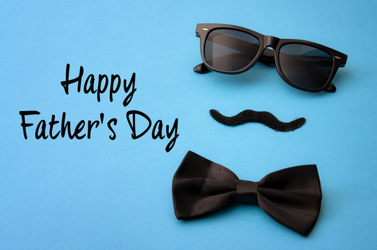 Father day and male hipster fashion concept with minimalist image of a pair of square sunglasses, black bowtie and a fake moustache on colorful blue background