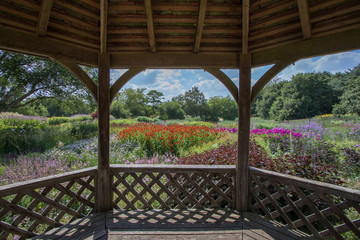 Wooden garden gazebo with landscape view of beautiful flower plants