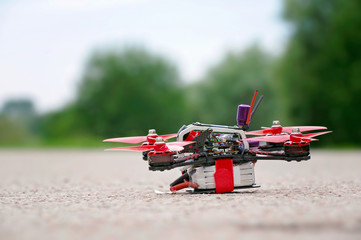 Racing drone stands on ground ready to fly. Close up view. Blurred background