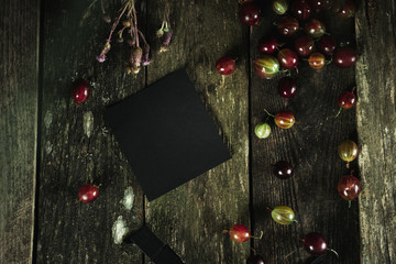 blank black sheet with copyspace for text and design. Gooseberry scattered on a wooden old texture table background. Top view Close up food photo in a dark low key.