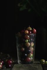 Food photo of a gooseberry in glass on a wooden old texture background. Photography in a dark low key. Macro shot
