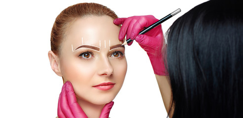 Wide studio picture of a beauty specialist marking out eyebrows shape