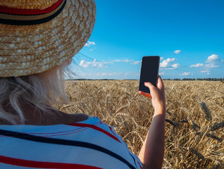 girl takes pictures of a wheat field