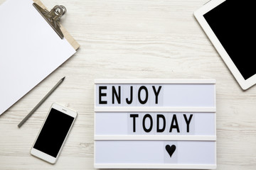 Work space with tablet, smartphone, notepad and 'Enjoy today' word on lightbox over white wooden background, top view. From above, flat-lay, overhead. Copy space.