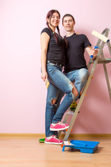 Photo of young woman and man with paint roller standing near staircase