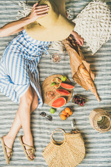 Summer picnic setting. Young woman in striped dress and straw sunhat sitting with rose wine, fresh fruit on board and baguette on blanket, top view. Outdoor gathering or lunch concept