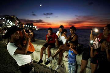 People record videos with their mobile phones of a street musician's performance during sunset at an internet hotspot along the seafront in Havana, Cuba