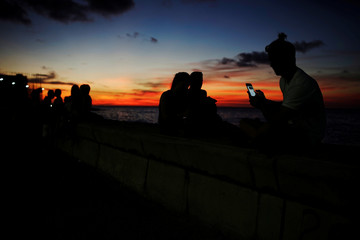 A man chats on the internet with his mobile device during sunset at a hotspot along the seafront in Havana, Cuba