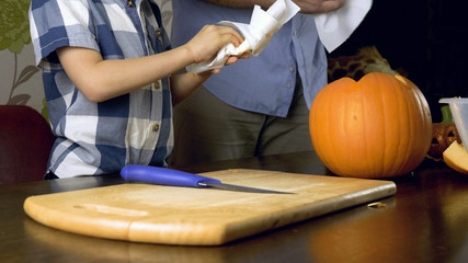 Young boy with his father carving a pumpkin for Halloween on a table