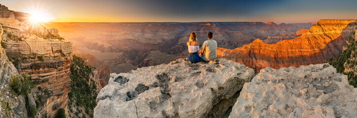 A man and a woman sit at the edge of the Grand Canyon at sunset minutes