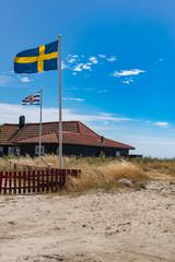 Swedish flag outside a coast house. Picturesque beach landscape. Stock photo.