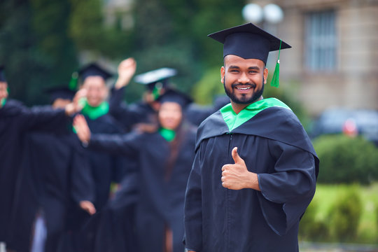 portrait of successful indian student in graduation gown thumb up