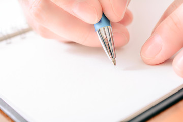 Close-Up Of A Male Hand Writing In A Blank Organizer With A Biro