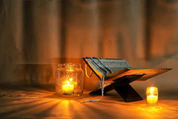 The Quran is placed on a wooden stand.Light candles.