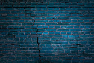 texture of a wall of blue brick with long thin crack and dark edges