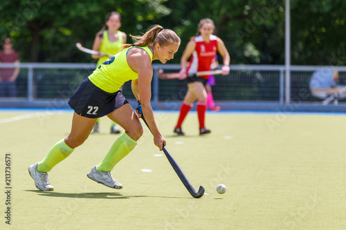 Young Hockey Player Woman With Ball In Attack Playing Field Hockey
