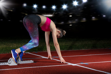 woman sprinter leaving starting blocks on the athletic track. exploding start on stadium with reflectors