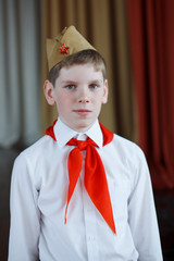 A modern boy with a red pioneer tie in a white shirt and a soldier's cap with a red star at a solemn meeting in honor of the Great Victory Day.