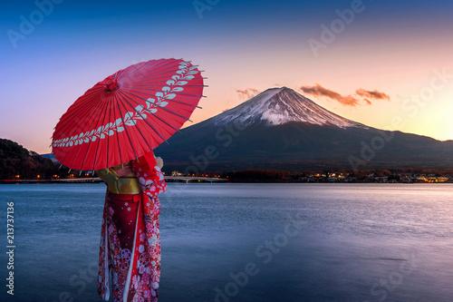 Wall mural Asian woman wearing japanese traditional kimono at Fuji mountain. Sunset at Kawaguchiko lake in Japan.