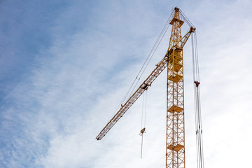 building construction site with yellow tower crane against blue sky