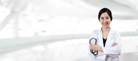 Portrait of young attractive female asian doctor or physician crossed arms holding stethoscope medical equipment, smiling and looking at camera in hospital feeling professional confident for banner.
