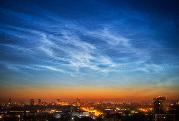 Noctilucent clouds over the city downtown at summer night