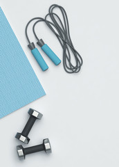 Fitness mat, dumbbells and jumping rope on the floor