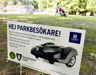 A sign alerts visitors about a presence of Husqvarna robotic lawn mower at work in the Humlegarden park in Stockholm