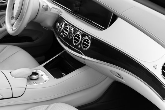 White leather interior of the luxury modern car. Leather comfortable white seats and multimedia. Steering wheel and dashboard. Automatic gear shift. Car interior details. Black and white