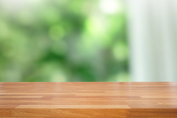 Empty of wood table top on blur of abstract green from garden with sunlight and curtain window