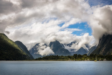Panoramic View of Mountain peaks and glacier engulfed in the clouds in the background and Milford Sound Marina in the foreground, in Fiordland National Park, New Zealand
