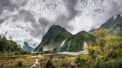 Impressive weather conditions with clouds raising and engulfing the mountain at Milford Sound in Fiordland National Park, New Zealand.