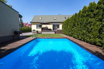 Swimming pool in the garden of house with trees during summer. Real photo