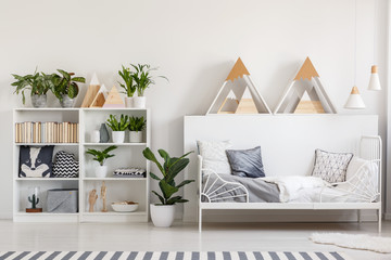 Wooden rack with books, fresh plants and cushions in white bedroom interior with fluffy rug next to metal bed